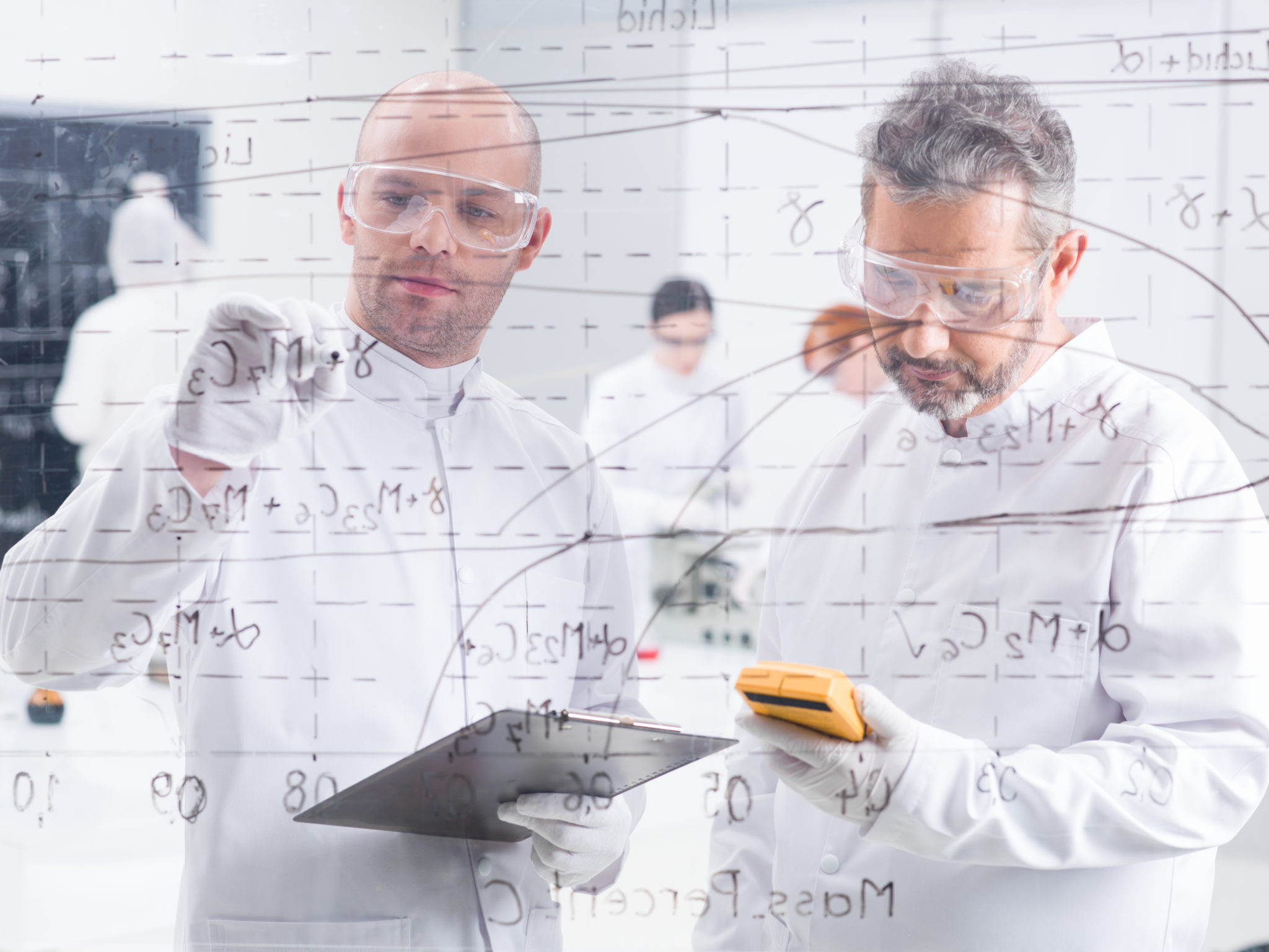 Close-up,Of,Two,Researchers,In,A,Lab,Writing,Formulas,On