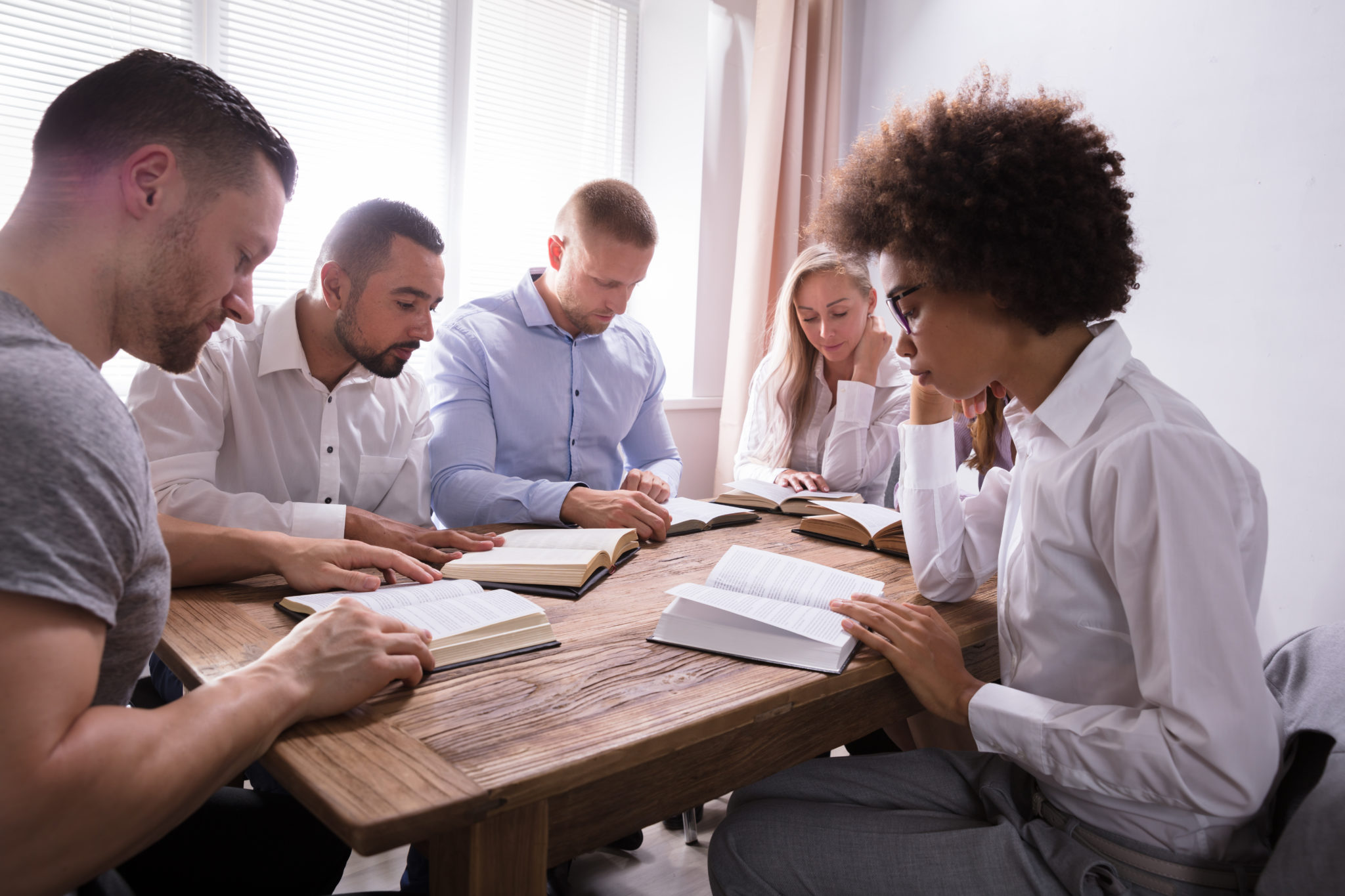 Group,Of,Young,Multiethnic,People,Reading,Bible,Over,Wooden,Desk